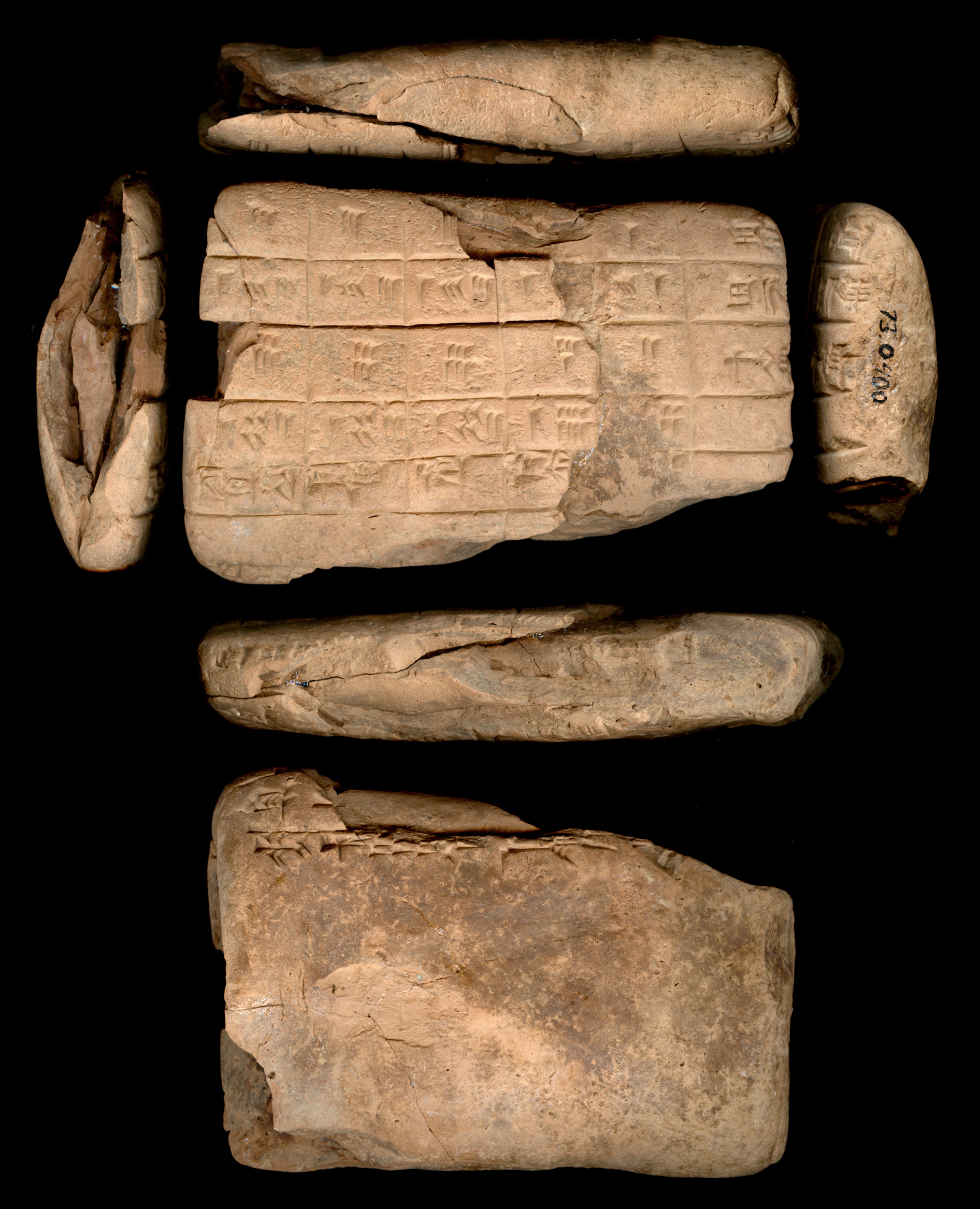 Pieces of a clay tablet with inscriptions. Several pieces just have a little inscription along one edge, but the one piece is entirely divided into rows and columns. Each cell contains a few characters of some language.