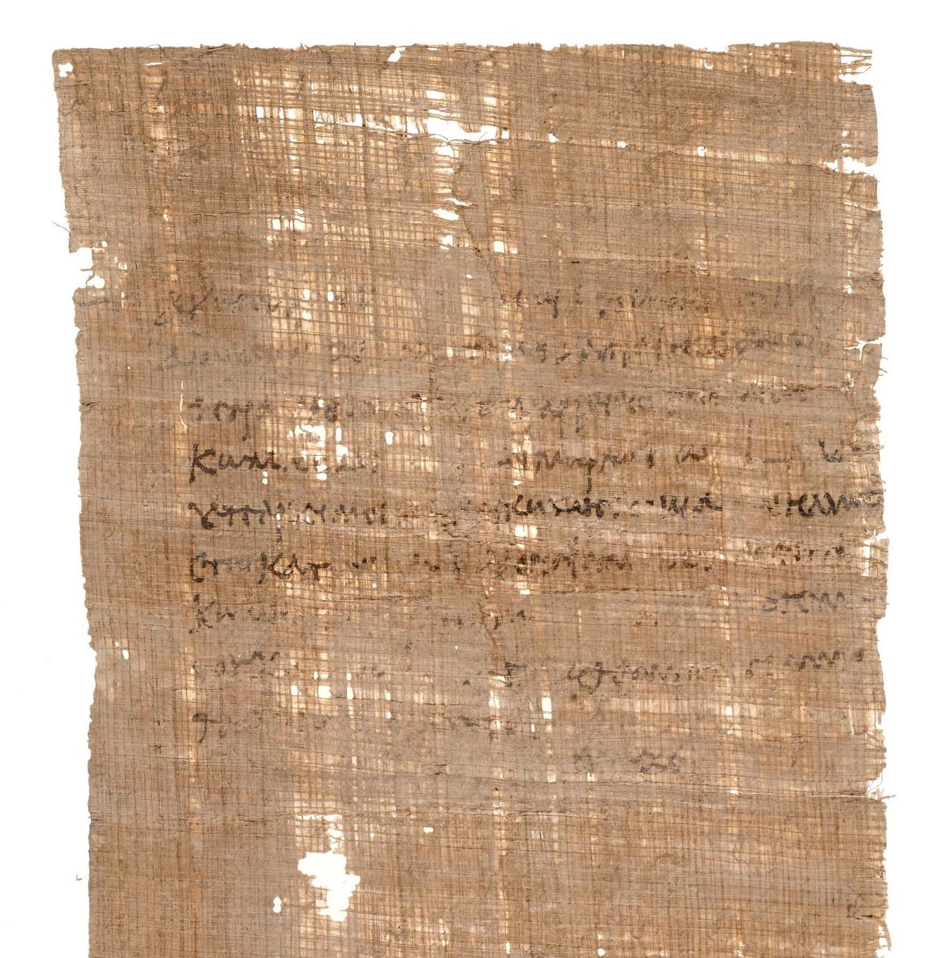 Rectangular piece of light brown material, threadbare with with some holes, with lines of handwriting on it in variably faded ink.