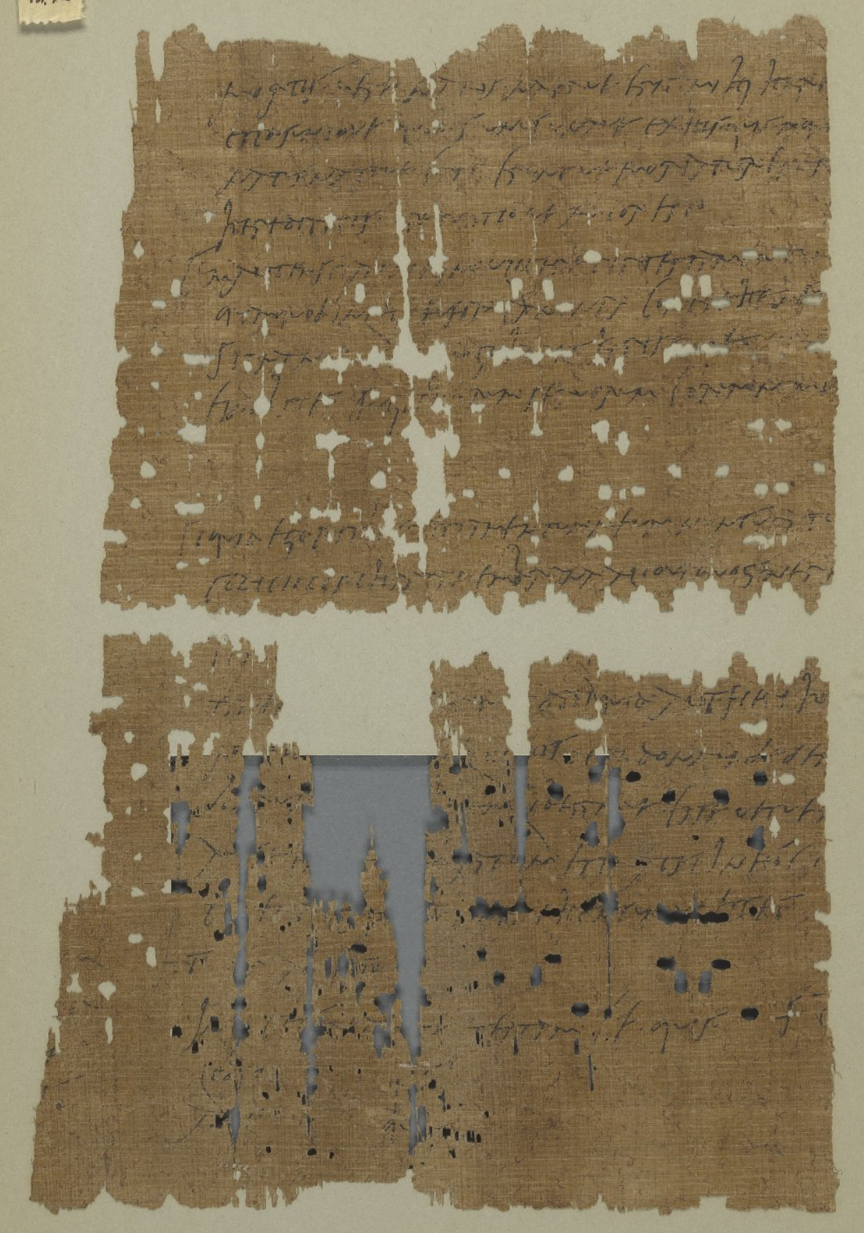 Tattered fragments of a sheet of papyrus with horizontal lines of handwritten text in dark but partially faded ink