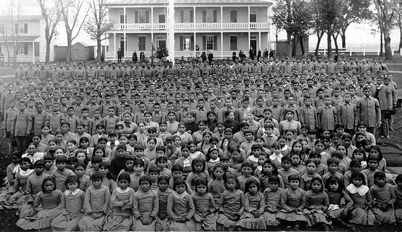 A group photo of hundreds of Native American children and teenagers, few if any of them smiling, lined up in front of a school building