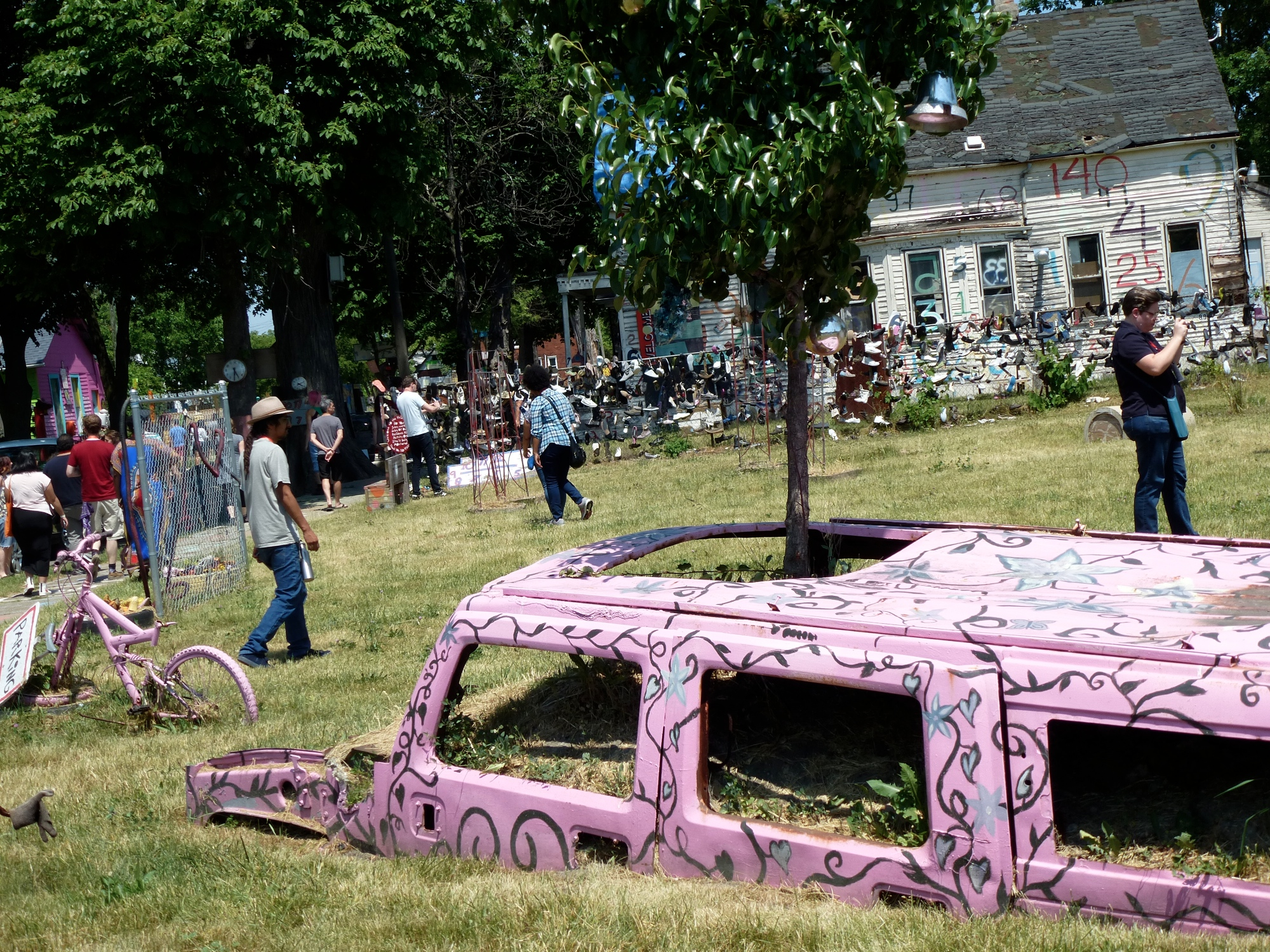 A Hummer appears to be half buried in the ground. Its windowless frame is painted matte pink with vine-like designs. A small tree grows out of its sunroof. In the background are a house, other outdoor art pieces, and people of various races and genders looking at them.